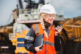 Lady in a construction site talking on the radios